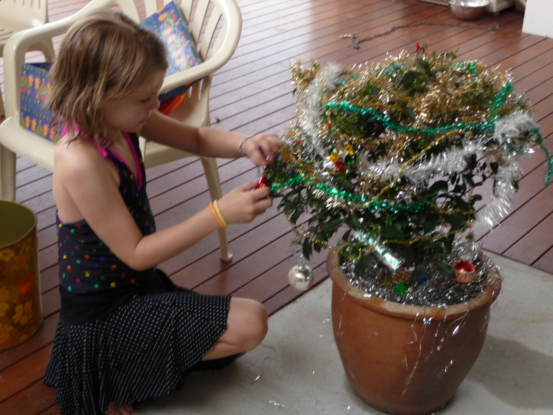 Girl decorating home grown Christmas tree