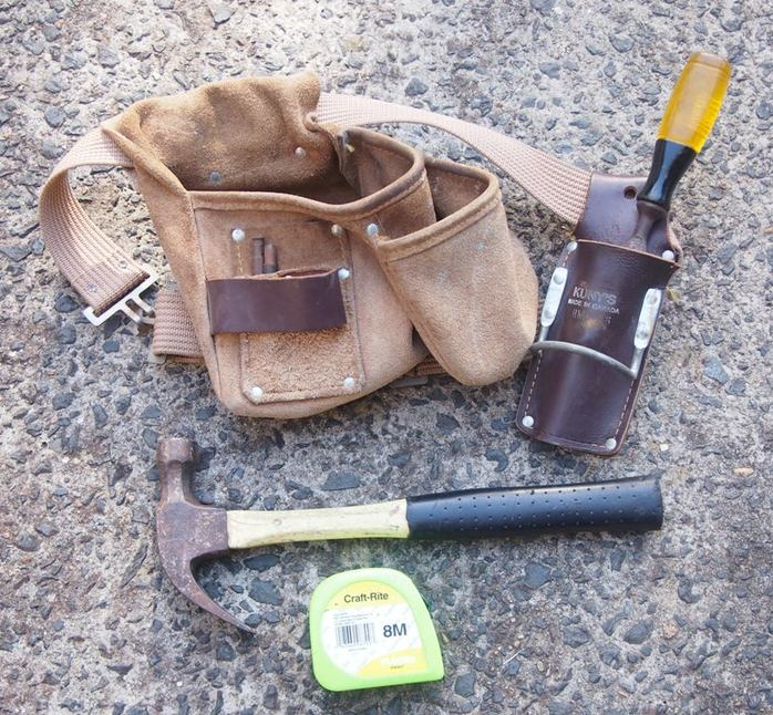 A carpenters nialbag, chisel, hammer and tape.