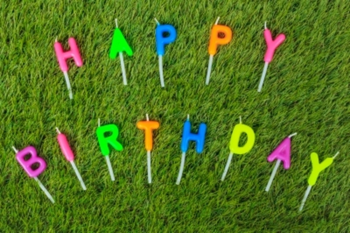 Happy Birthday spelled in colourful notes on grass